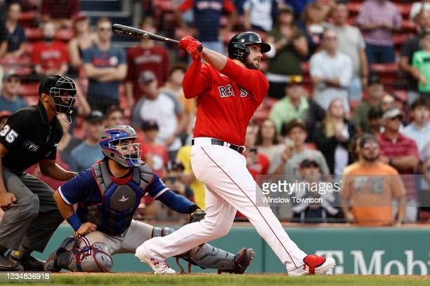 As catcher Jose Trevino of the Texas Rangers looks on, Travis Shaw of the Boston Red Sox follows through on his game winning grand slam during the...