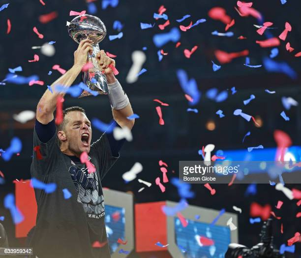 As confetti falls around him New England Patriots quarterback Tom Brady howls as he hoists the Vince Lombardi Trophy following New England's...