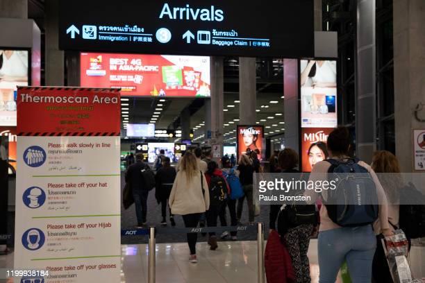 As Coronavirus spreads travelers arriving wear masks walking through a thermal scanner at Suvarnabhumi International airport in Bangkok, Thailand on...