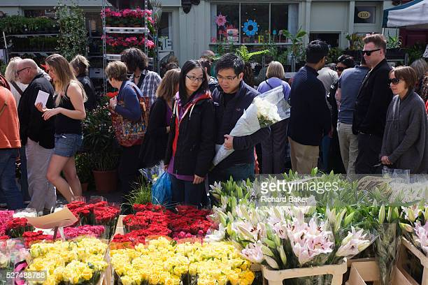 As crowds walk past fresh roses and lilies in Columbia Road flower market in north London a young Asian couple browse other blooms on show Beautiful...