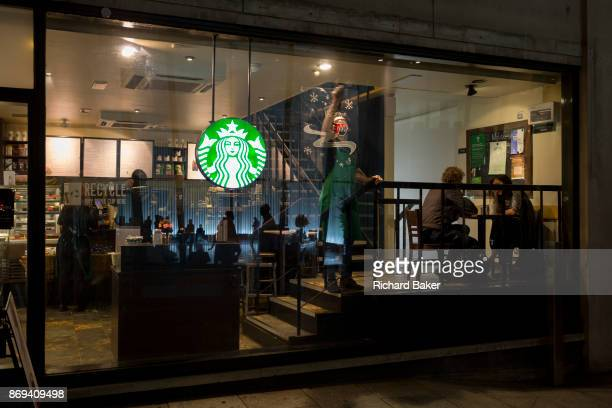 As customers talk a Starbucks employee places a Christmas poster to the window of a coffee shop on Walbrook in the heart of the Square Mile the...