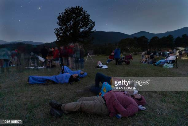 As darkness falls people lie on the ground to view the Perseid meteor shower in Rocky Mountain National Park in Colorado at an astronomy night event...