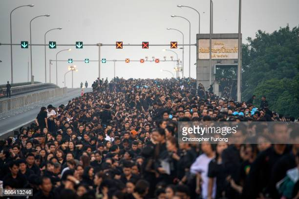 As dawn breaks thousands of people queue on a bridge to attend the funeral of the late Thai King Bhumibol Adulyadej on October 26 2017 in Bangkok...