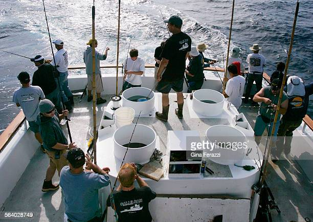 As deckhand Dave Grudzien stands on the bait hold passengers aboard the 60–foot Gallilean fish for albacore tuna 80 miles off the coast of San Diego...