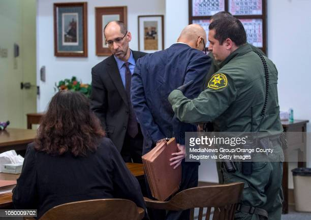 As defense attorneys Denise Gragg left and Ken Morrison second from left look on a handcuffed Andrew Urdiales an eighttime serial killer is lead by...