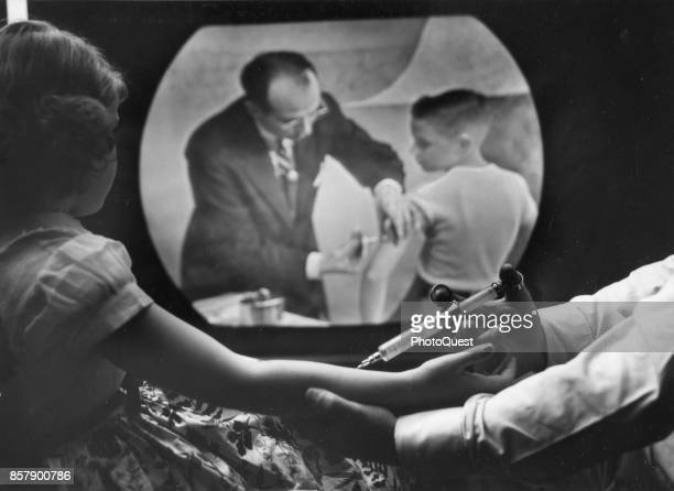 As eightyearold girl receives a polio vaccine she watches a closed circuit television broadcast of a training telecast for physicians and scientists...