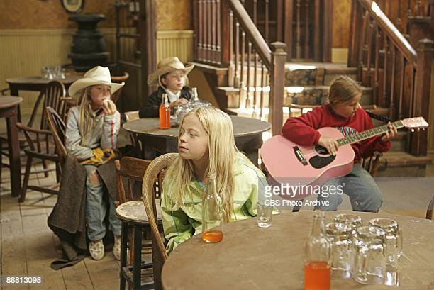 As Emilie plays her guitar Leila relaxes as Randi and Sophie enjoy their refreshments in KID NATION on the CBS Television Network