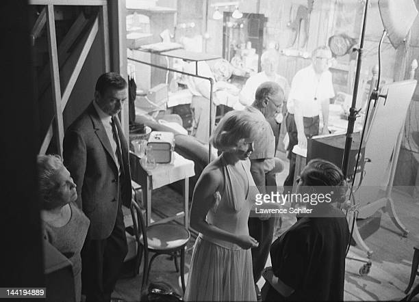 As French actor Yves Montand waits his costar American actress Marilyn Monroe talks with her dialogue coach Paula Strasberg during the filming of...
