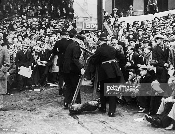 As Fulham play Millwall at Fulham's Craven Cottage ground police remove one of the barriers after it collapsed under pressure from the huge crowd 8th...
