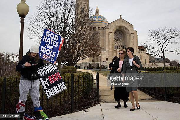 As funeral attendees walk by a member of the Westboro Baptist Church protests outside of the Basilica of the National Shrine of the Immaculate...