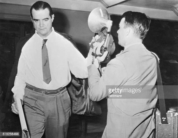 As he departed from the courtroom where Howard Hughes' left hand is apparently doing TV cameraman Harry Watson's camera no good Hughes denies that he...