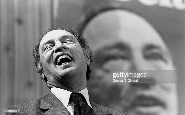 As he stands in front of an oversize photo of himself Canadian politician and Prime Minister Pierre Trudeau throws his head backs and laughs Canada...