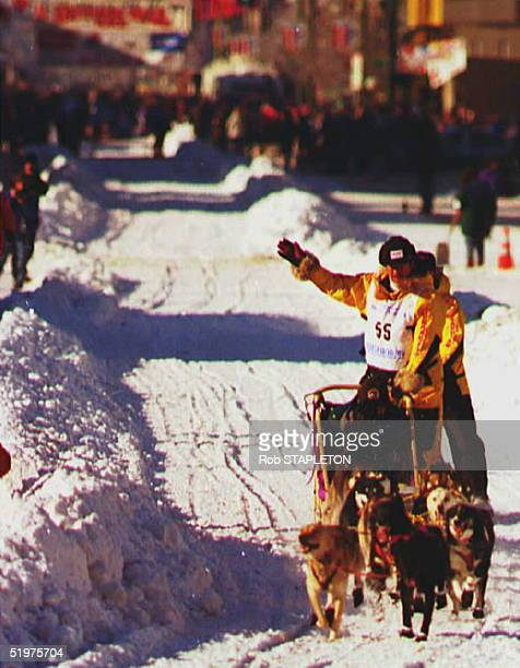 As he starts the Iditarod dogsled race five time Iditarod champion Rich Swenson waves at crowds lining the street in Anchorage Alaska early 02 March...