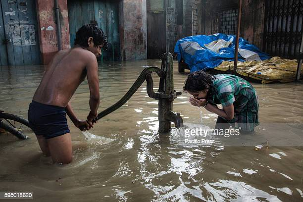 As heavy rainfall and rising river Ganges water level flooded Kalighat area of Kolkata city a man helps a girl with drinking water from a hand tube...