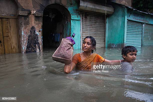 As heavy rainfall and rising river Ganges water level flooded Kalighat area of Kolkata city a mother tries the wade through with her boy The low...