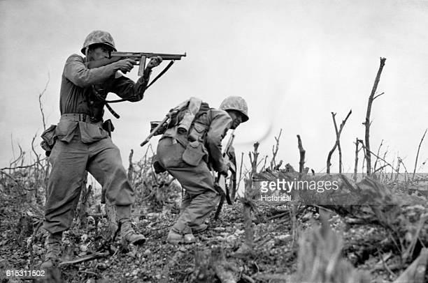 As his companion ducks for cover, a U.S. Marine aims his sub-machine gun at a Japanese sniper at Wana Ridge before the town of Shuri on South...