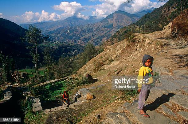 As his mother washes clothes in a communal spring below a young boy of about 9 years of age stands on a track in the Himalayan foothills near the...