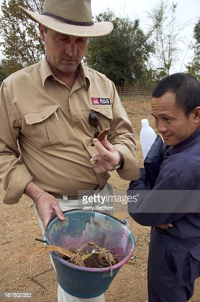 As his translator Khamla looks on, Stuart Broome, a Technical Field Manager with the Mines Advisory Group, examines a bucket-full of scrap metal his...