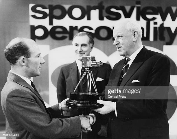 As host Peter Dimmock looks on racing driver Stirling Moss receives the Sportsview Sports Personality of the Year trophy for his outstanding...
