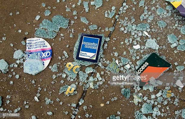 As if about to be crunched underfoot shattered glass from the windows of offices in the historic City of London sidestreet stickers and notices for...