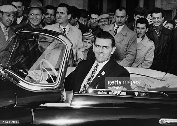 As interested spectators look on Montreal Canadiens' ace hockey player Maurice 'The Rocket' Richard sits behind the wheel of the sports car he was...
