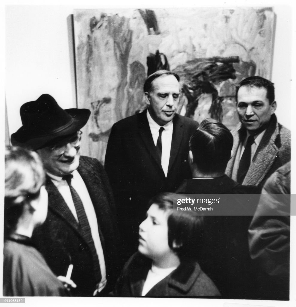 As Latvian-born American painter Mark Rothko (1903 - 1970) (in hat) talks with editor Rose Slivka (1919 - 2004) (extreme left), Canadian painter Philip Guston (1913 - 1980) (center rear) attends an exhibition of his work at Sidney Janis Gallery, New York, New York, December 28, 1959.
