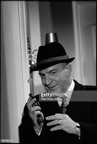 As Lt Theo Kojak American actor Telly Savalas in an overcoat and hat holds a gun in a scene from the television movie 'The MarcusNelson Murders'...