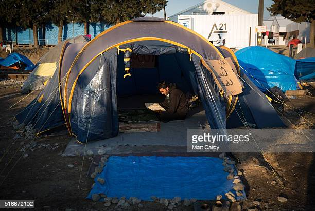 As man reads a prayer book in a tent as the sun rises at the Idomeni refugee camp on the Greek Macedonia border on March 20 2016 in Idomeni Greece...