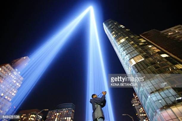 As man takes a pictures as the The 'Tribute in Light' illuminates the night sky on September 10 2017 in New York City on the eve of the anniversary...