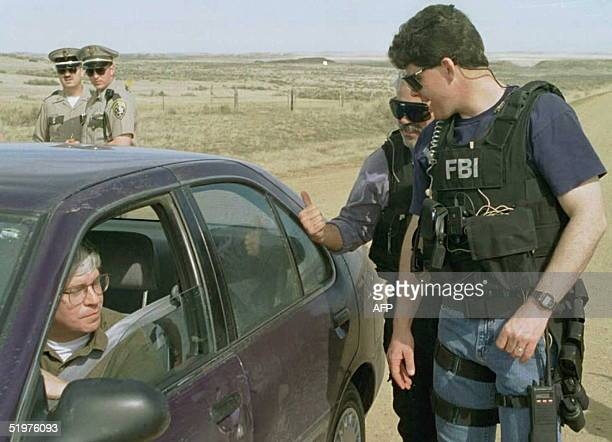 As Montana State Police officers watch in background two FBI agents inspect the vehicle of an unidentified motorist at a roadblock close to the...