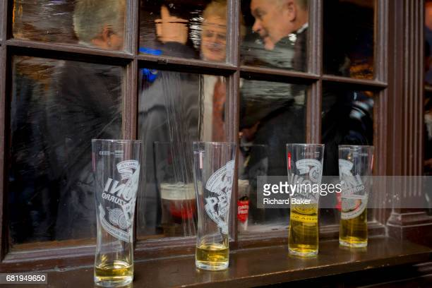 As nearlyempty lager glasses are lined up on a sill of a City on Lime Street male businessman enjoy afterwork drinks on 10th May 2017 in the City of...
