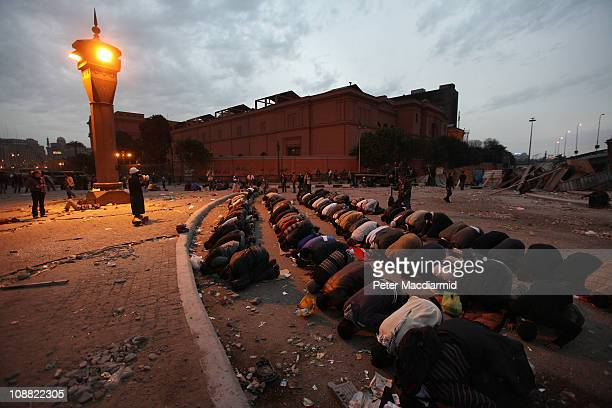 As night falls antigovernment demonstrators pray in Tahrir Square in sight of The Egyptian Museum on February 4 2011 in Cairo Egypt Antigovernment...