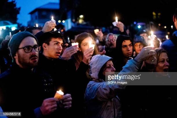 As night fell on the crowd a new energy of togetherness arose with the music and song while mourners hold candles Aftermath of the mass shooting at...