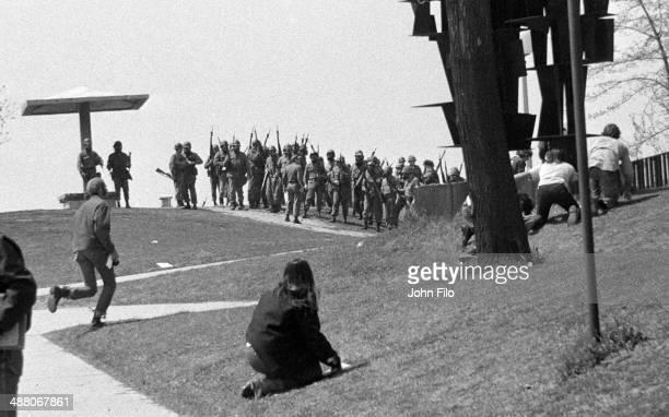 As Ohio National Guard troops march on campus students crouch down to take cover during an antiwar demonstration at Kent State University Kent Ohio...