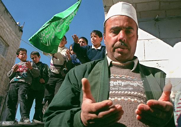 As Palestinian boys wave an Islamic flag a Palestinian man prays January 14 2001 during the funeral of Shaker Hassouni in the West Bank town of...