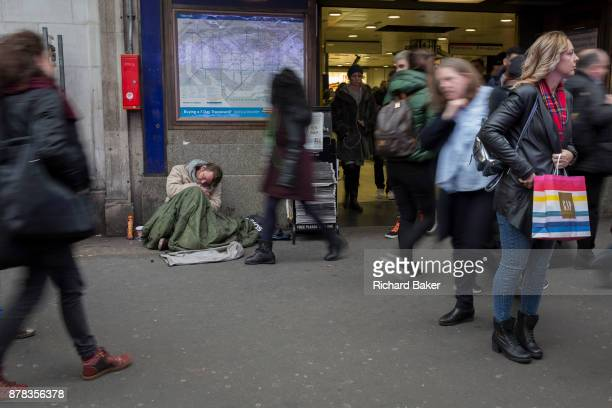 As passersby blur when walking past a homeless street beggar sleeps on the ground outside Holborn tube station on 22nd November 2017 in London England