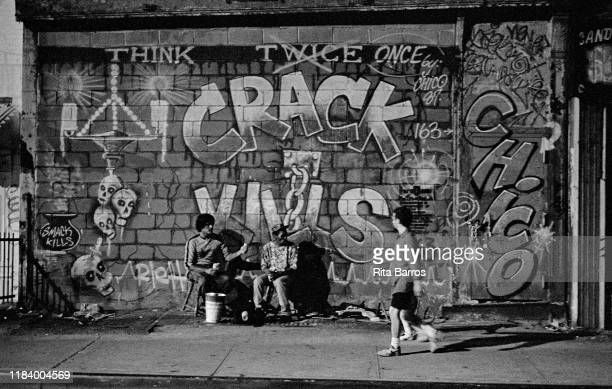 As pedestrian walks past, two men sit on chairs in front of a sidewalk mural, 'Crack Kills' , New York, New York, 1990.