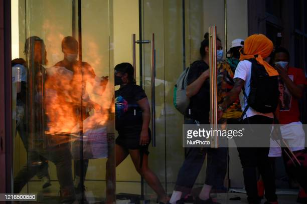 As people gain access flames from a police car set ablaze are reflected in the glass doors of the Apple Store on Walnut Street in Philadelphia PA on...