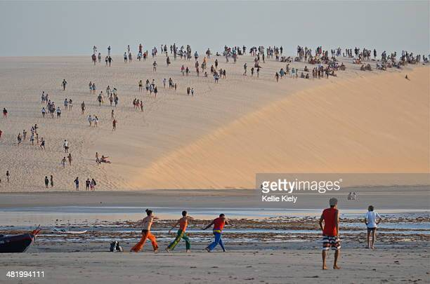 As people hike Jericoacoara's giant sand dune to view the sunset, three locals practice the native Brazilian martial arts dance, Capoeira
