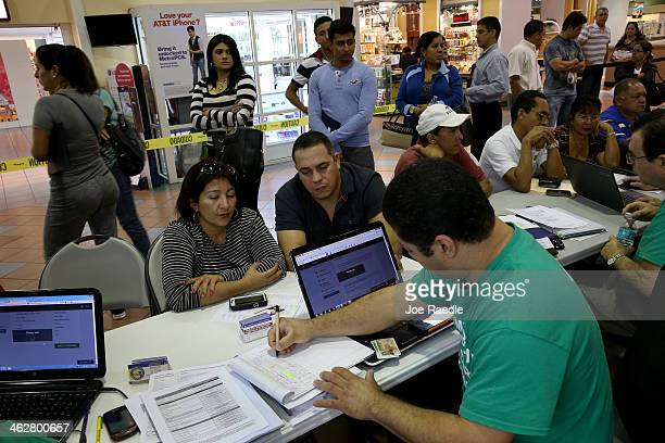 As people stand in line to speak with an insurance agent Marlene LimaRodriguez and Javier Gonzalez sit with Denis Garcia an insurance agent from...