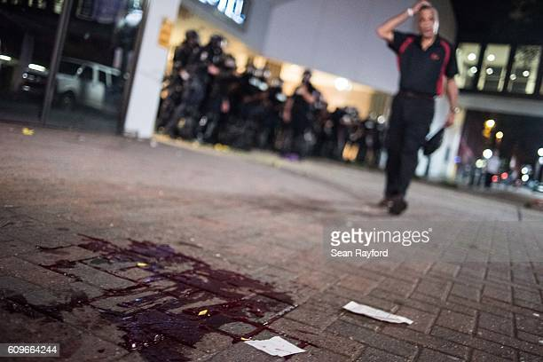 As police officers guard the garage entrance to the Omni Hotel, a man approaches blood on the sidewalk September 21, 2016 in Charlotte, NC. Protests...