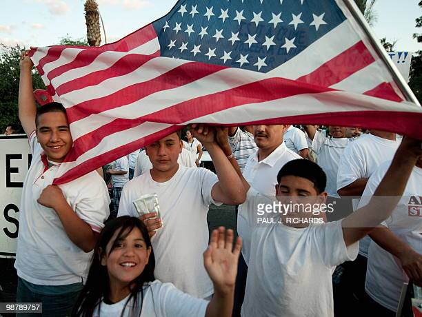 As protestors gather around the Arizona State Capitol against the State Senate bill 1070 May 1 at sunset kids wave the US flag AFP Photo/Paul J...