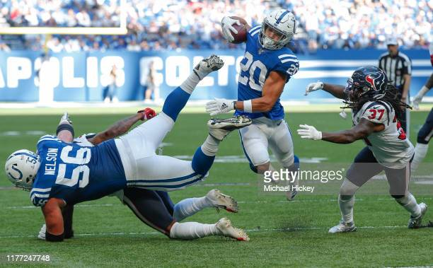 As Quenton Nelson of the Indianapolis Colts makes a hole for him Jordan Wilkins of the Indianapolis Colts rushes the ball as Jahleel Addae of the...