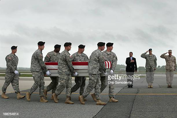 As rain pours out of the sky a US Army carry team carries the flagdraped transfer case with the remains of Army Spc Thomas Paige Murach Meridian...