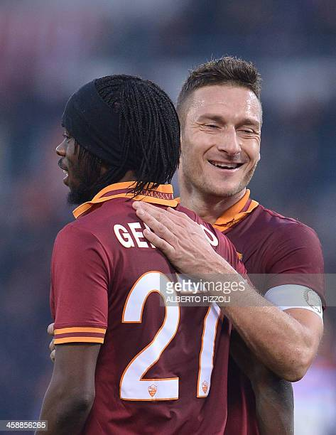 As Roma's forward Gervinho is congratulated by teammate Francesco Totti after scoring during the Italian Serie A football match As Roma vs Catania on...