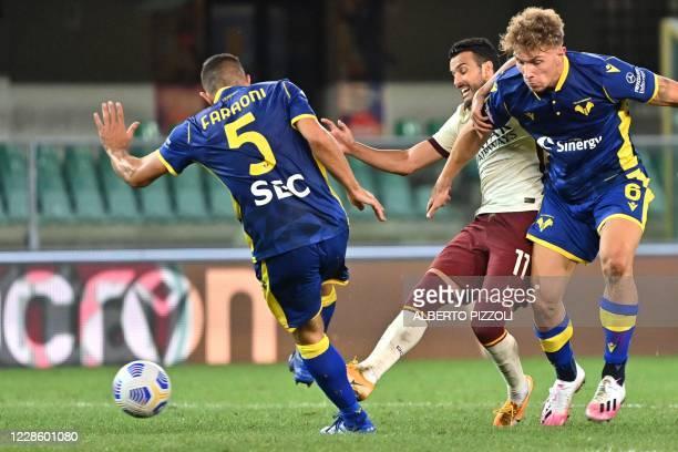 As Roma's forward Pedro challenges Verona's Italian defender Davide Faraoni and Verona's Italian defender Matteo Lovato during the Italian Serie A...
