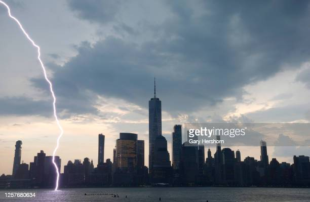 As seen from Jersey City, New Jersey, a bolt of lightning hits the middle of the Hudson River in front of lower Manhattan and One World Trade Center...