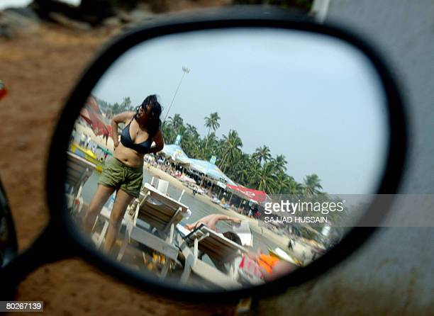 As seen from the reflection in the rearview mirror of a motorcycle tourists relax on sunbeds at Baga beach in Goa on March 16 2008 Continuing her...