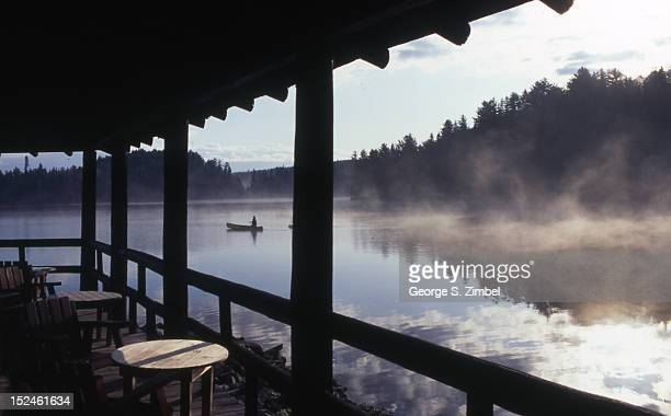 As seen from the verandah of the Arowhon Pines Lodge fog rises on Little Joe Lake while in a the distance a man fishes from a canoe Algonquin Park...