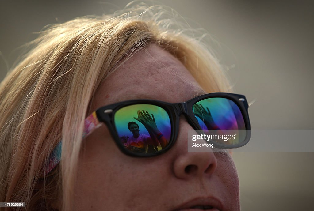 As seen on reflection on her glasses, Katherine Nicole Struck of Frederick, Maryland, hi-fives another same-sex marriage supporter outside the U.S. Supreme Court June 26, 2015 in Washington, DC. The high court ruled that same-sex couples have the right to marry in all 50 states.